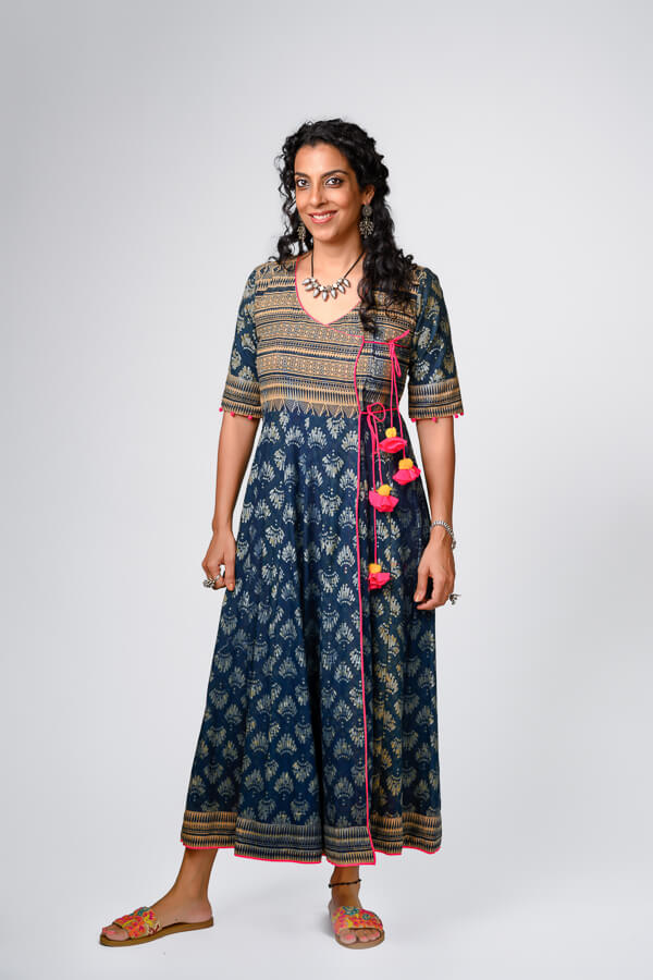 Flared mulmul Angarkha wrapped dress with resist hand block printing. Dyed in natural Indigo, this dress is surely a winner straight to the heart. Comfortable and elegant, can be teamed-up with pants. Fuscia pink detailing at the seam and bottom hem. Attractive handcrafted flower ties.